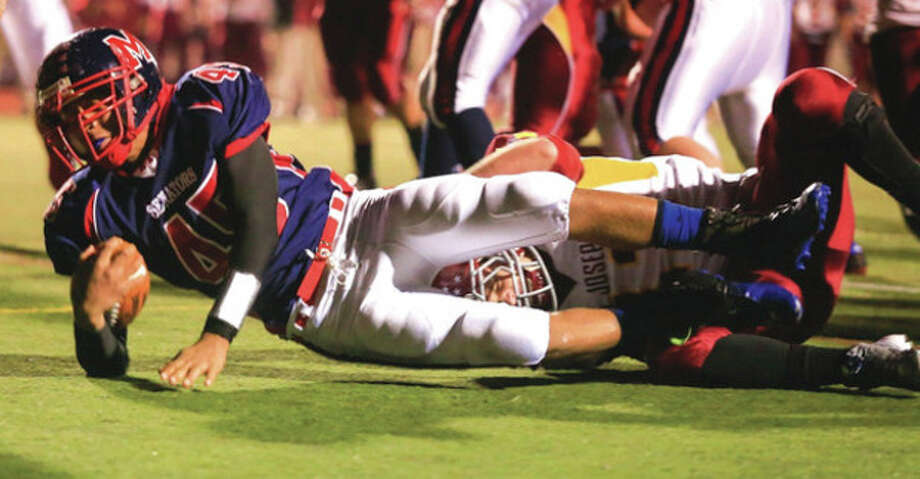 Hour photo/Chris PalermoBrien McMahon's Kenneth Keen is taken down by a St. Joseph defender but not before reaching the end zone during Friday night's game at BMHS. The visiting Cadets came back to hand McMahon a 42-35 defeat in a high-scoring affair. / © 2013 Hour Newspapers All Rights Reserved