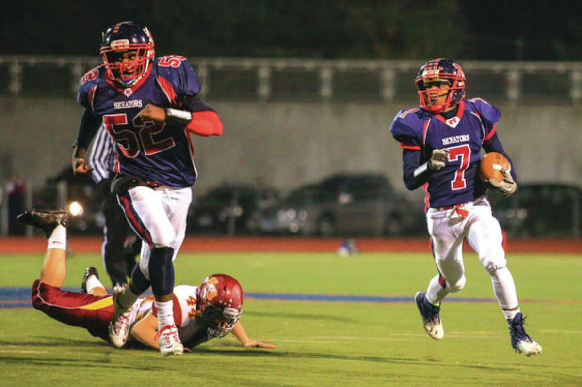 Hour photo/Chris Palermo Brien McMahon's Kentrell Snider, right, runs the ball upfield during Friday night's game against St. Joseph at BMHS. Snider had a big second-half TD for the Senators, but St. Joe's came back for a 42-35 victory. McMahon's Rutho Charlot (52) provides the blocking for Snider.