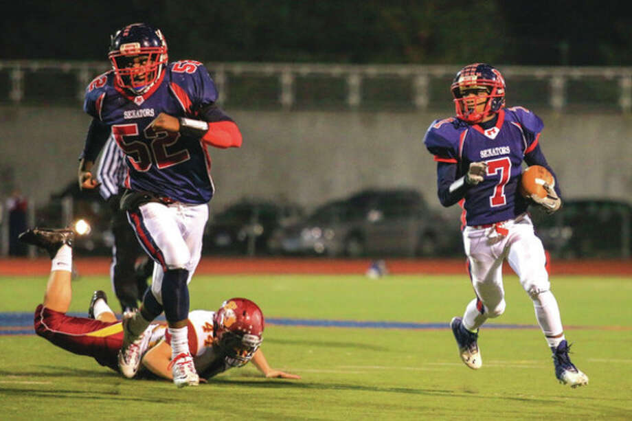 Hour photo/Chris PalermoBrien McMahon's Kentrell Snider, right, runs the ball upfield during Friday night's game against St. Joseph at BMHS. Snider had a big second-half TD for the Senators, but St. Joe's came back for a 42-35 victory. McMahon's Rutho Charlot (52) provides the blocking for Snider. / © 2013 Hour Newspapers All Rights Reserved