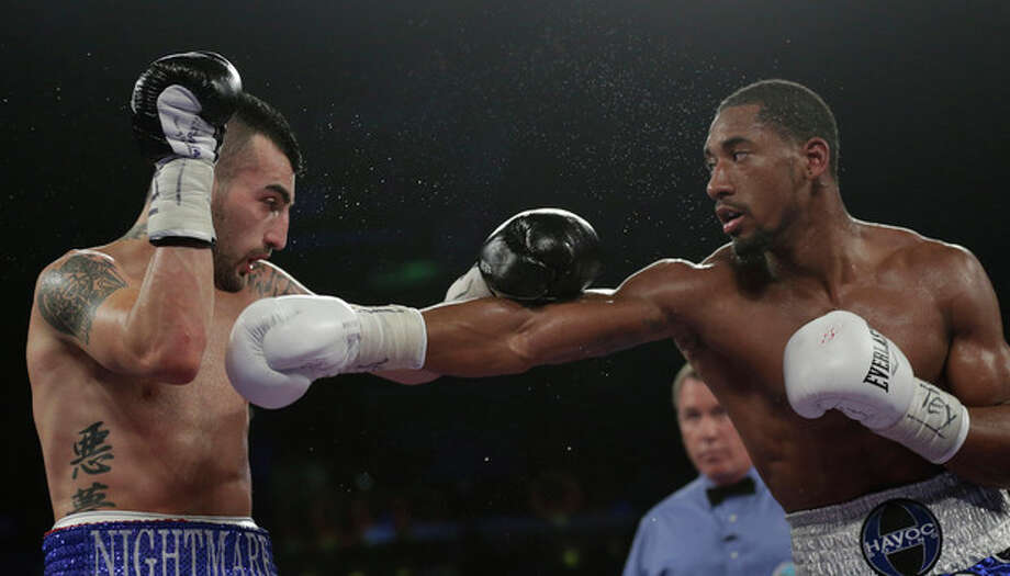 Demetrius Andrade, right, hits Vanes Martirosyan, left, during round 7 of a WBO junior middleweight title bout, Saturday, Nov. 9, 2013, in Corpus Christi, Texas. (AP Photo/Eric Gay) / AP