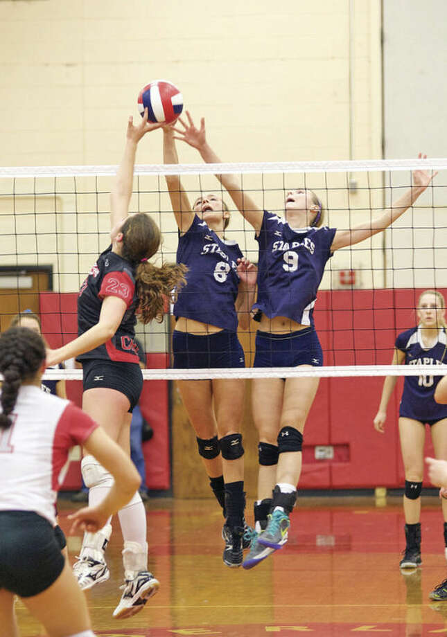 Hour photo/Danielle CallowayStaples' blockes Knox McKay (8) and Lauren Mushro (9) defend the net during the CIAC Class LL State Championship game against Cheshire at Berlin High School Saturday evening.