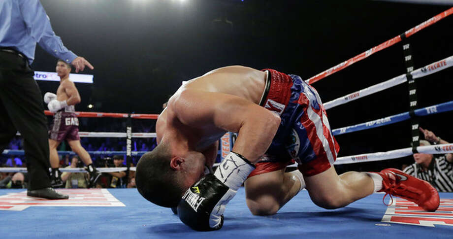 Roman Martinez, right, goes down for the count as Mikey Garcia, left, watches during round 9 of a WBO Super Featherweight title bout, Saturday, Nov. 9, 2013, in Corpus Christi, Texas. (AP Photo/Eric Gay) / AP