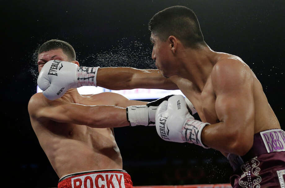 Mikey Garcia, right, lands a punch on Roman Martinez, left, during round 3 of a WBO Super Featherweight title bout, Saturday, Nov. 9, 2013, in Corpus Christi, Texas. (AP Photo/Eric Gay) / AP