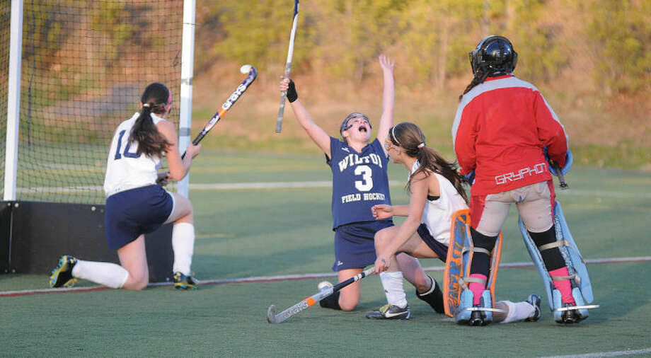 Hour photo/John Nash - Wilton's Emilie Arrix, center, reacts after the Warriors scored the game's only goal in a 1-0 overtime win over Lauralton Hall, to win the program's third straight Class M state championship.