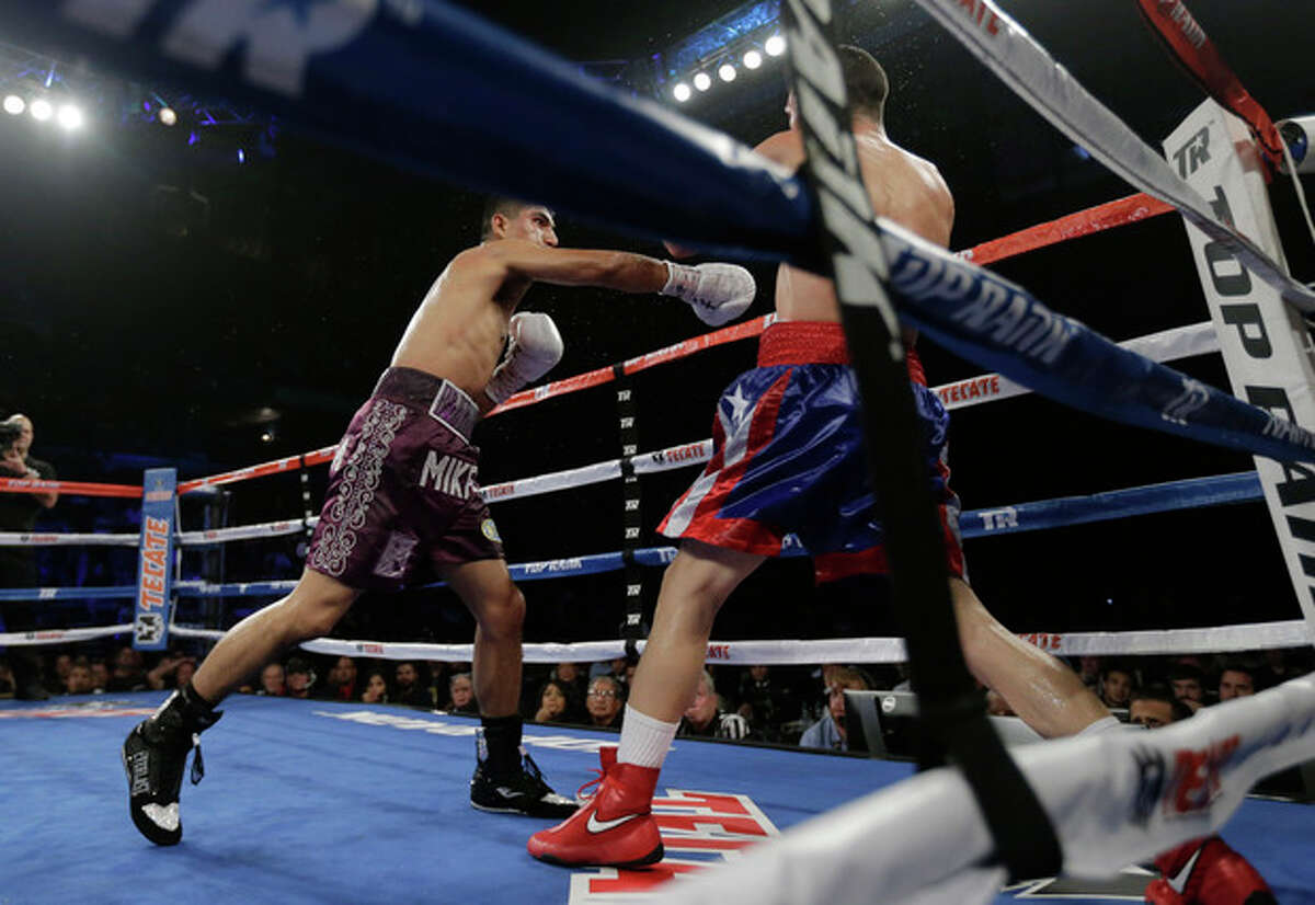 Mikey Garcia, left, knocks Roman Martinez, right, into the ropes round 9 of a WBO Super Featherweight title bout, Saturday, Nov. 9, 2013, in Corpus Christi, Texas. (AP Photo/Eric Gay)