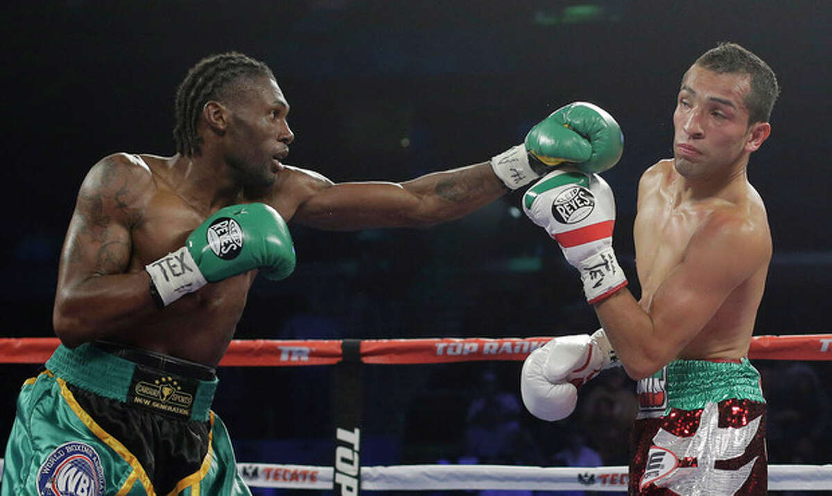 Nicholas Walters, left, throws a punch at Alberto Garza, right, during the second round of a WBO featherweight title bout, Saturday, Nov. 9, 2013, in Corpus Christi, Texas. Walters won with a knockout in the 4th round. (AP Photo/Eric Gay)