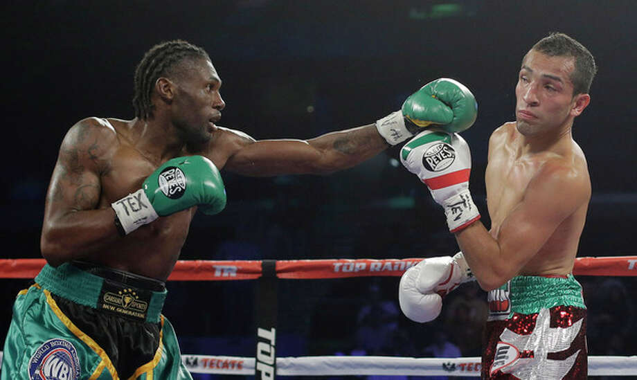 Nicholas Walters, left, throws a punch at Alberto Garza, right, during the second round of a WBO featherweight title bout, Saturday, Nov. 9, 2013, in Corpus Christi, Texas. Walters won with a knockout in the 4th round. (AP Photo/Eric Gay) / AP