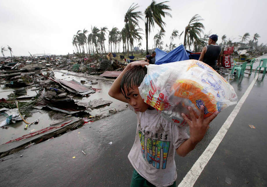 A boy carries relief goods, walking past the devastation caused by Typhoon Haiyan, in Tacloban city, Leyte province, central Philippines on Sunday, Nov. 10, 2013. Typhoon Haiyan, one of the most powerful storms on record, slammed into six central Philippine islands on Friday, leaving a wide swath of destruction and scores of people dead.(AP Photo/Aaron Favila) / AP