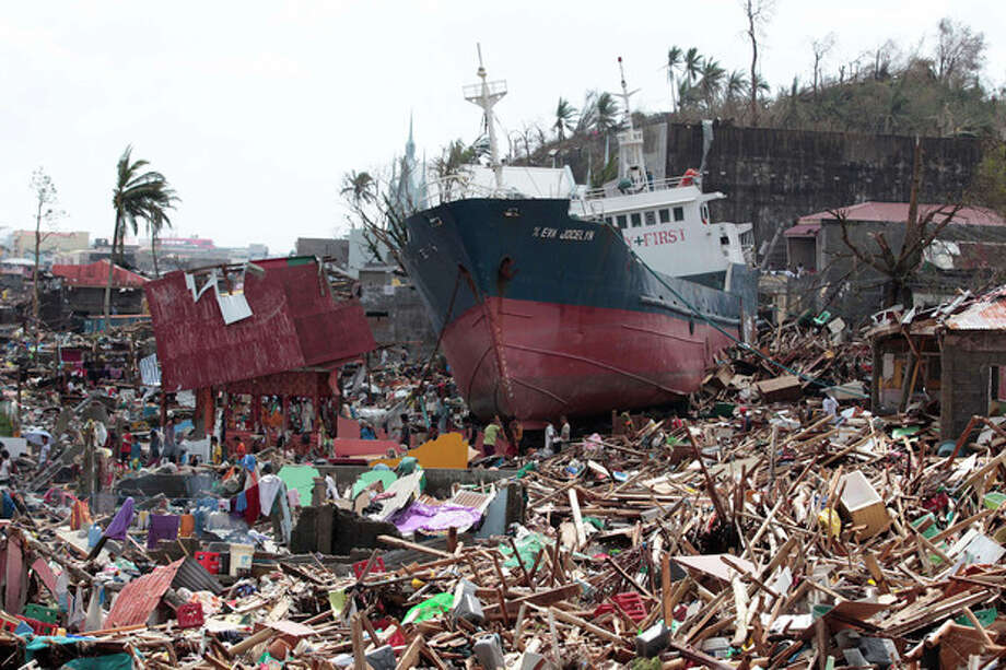 Survivors walk past a ship that lies on top of damaged homes after it was washed ashore in Tacloban city, Leyte province central Philippines on Sunday, Nov. 10, 2013. The city remains littered with debris from damaged homes as many complain of shortage of food, water and no electricity since the Typhoon Haiyan slammed into their province. Haiyan, one of the most powerful typhoons ever recorded, slammed into central Philippine provinces Friday leaving a wide swath of destruction and scores of people dead. (AP Photo/Aaron Favila) / AP
