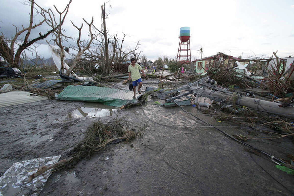 """A resident walks by toppled trees and electric posts after powerful Typhoon Haiyan slammed into Tacloban city, Leyte province, central Philippines on Saturday, Nov. 9, 2013. The central Philippine city of Tacloban was in ruins Saturday, a day after being ravaged by one of the strongest typhoons on record, as horrified residents spoke of storm surges as high as trees and authorities said they were expecting a """"very high number of fatalities."""" (AP Photo/Aaron Favila)"""