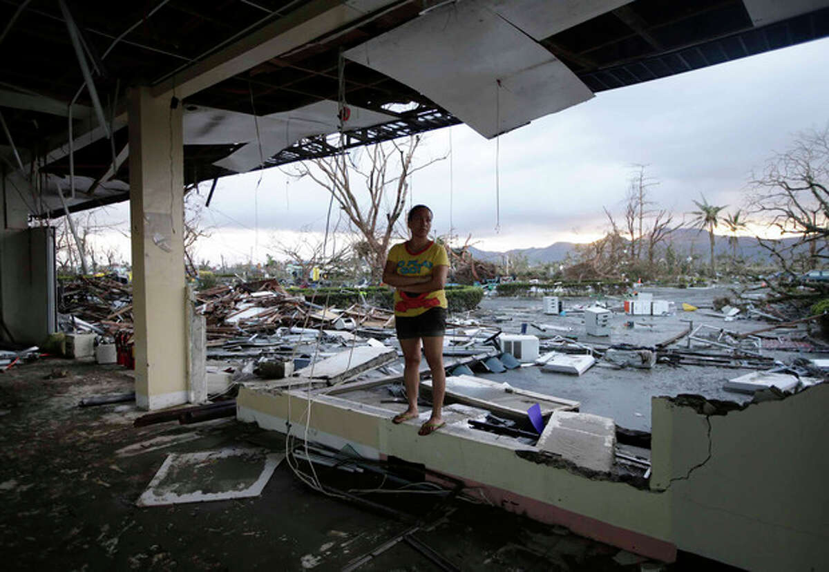 AP Photo/Bullit Marquez A woman stands amidst the devastation brought about by powerful Typhoon Haiyan at Tacloban city, in Leyte province, central Philippines Saturday Nov. 9.
