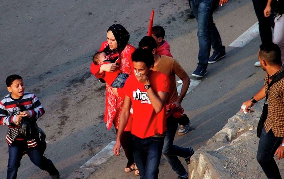 A mother rushes with her child during clashes between police and supporters of Egyptian club Al Ahly outside a stadium ahead of the African Champions League final in Cairo, Egypt, Sunday, Nov. 10, 2013. Police used tear gas Sunday to disperse the crowd as they threw rocks and tried to push their way into the stadium, many with no tickets. (AP Photo/Mostafa Darwish)