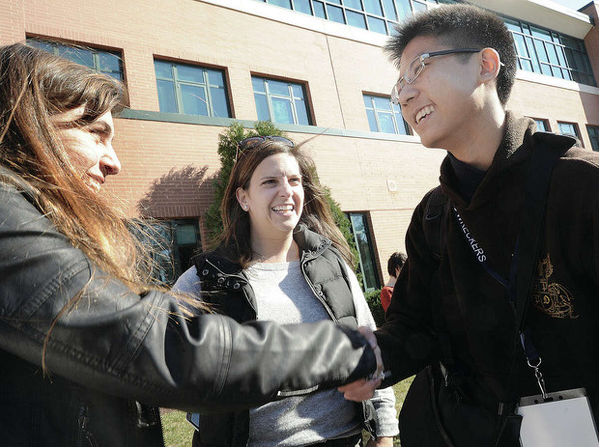 Hour photo/Matthew Vinci Amy Nebens introduces her daughter Sydney to Chinese student Xinyi Yang Sunday at Staples High School in Westport. Students from Singapore will stay with host families.