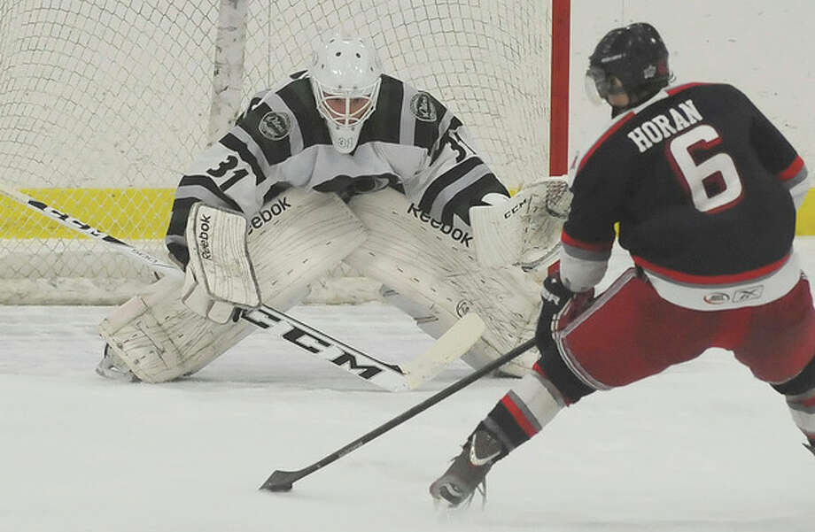 Hour photo/John NashConnecticut Oilers goaltender Nik Nugnes, left, focuses on making a save during this breakaway attempt by Hartford's Dave Horgan during the second period of Sunday's EHL game at the SoNo Ice House. The Oilers came away with a 5-1 victory over the Wolfpack.