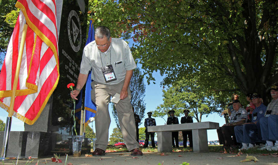In this Sept. 27, 2013 photo, Bob Marino, whose father was a World War II veteran in the 57th Bomb Wing, places a flower at the memorial to the 57th Bomb Wing as he takes part in a memorial ceremony during a reunion outside the U.S. Air Force Museum at Wright Patterson Air Force base in Dayton, Ohio. Marino, 72, a retired IRS attorney from Basking Ridge, N.J., helped organize the gathering. His Brooklyn-native father, Capt. Benjamin Marino, died in 1967 and left numerous photos from the war, and Marino set about trying to identify and organize them. To learn more about his father's experiences, he corresponded with other veterans. (AP Photo/Tom Uhlman) / FR31154