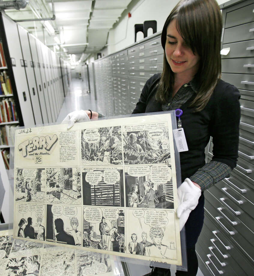 "In this Wednesday, Oct. 23, 2013 photo shows Caitlin McGurk holds up a cartoon titled ""Terry and the Pirates"" by Milton Caniff at the Billy Ireland Cartoon Library & Museum in Columbus, Ohio. The whole thing started with Caniff, the influential comic artist whose beloved ""Terry and the Pirates"" and ""Steve Canyon"" adventure strips lived in the nation's funny papers for a half century. Caniff graduated from Ohio State University and loved the place so much he wanted his original art and other papers to be kept here forever. (AP Photo/Tony Dejak) / AP"