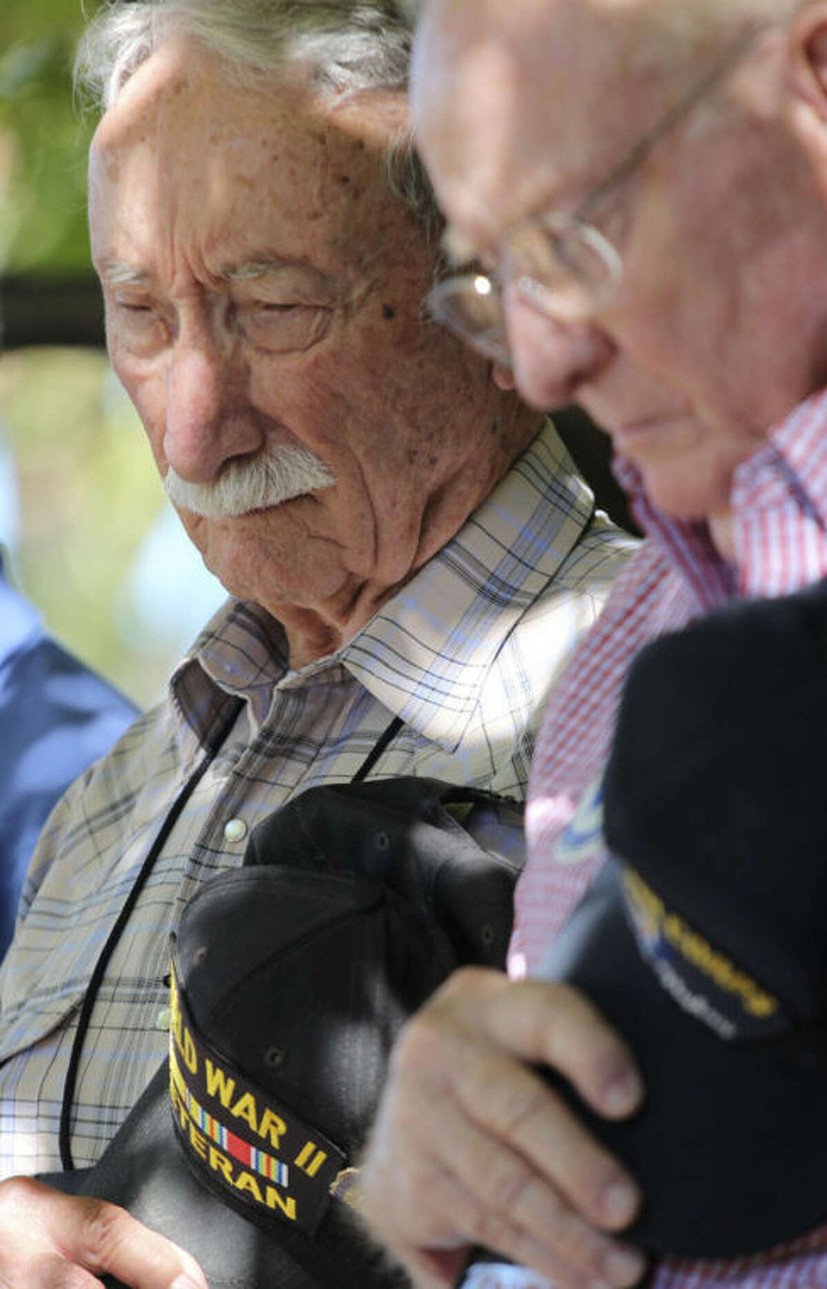 In this Sept. 27, 2013 photo, George Williams, left, and Robert Crouse, bow their heads as they take part in a memorial ceremony during a reunion outside the U.S. Air Force Museum at Wright Patterson Air Force base in Dayton, Ohio. As many as 11,000 people, including Williams and Crouse, served in the 57th Bomb Wing that flew missions over German-held Europe from North Africa and the island of Corsica during most of the war. Hundreds survive, according to wing historians and reunion organizers. Only nine veterans made it to this fall?'s event. (AP Photo/Tom Uhlman)
