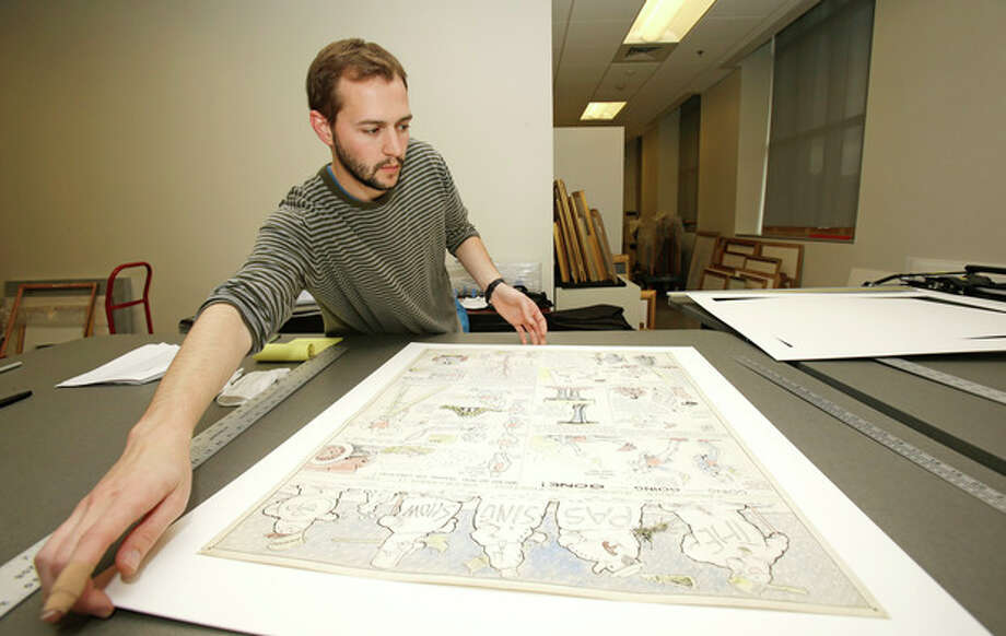 "In this Wednesday, Oct. 23, 2013 photo shows Jeremy Stone frames a Billy Ireland comic strip from Dec. 11, 1921 called ""The Passing Show"" at the Billy Ireland Cartoon Library & Museum in Columbus, Ohio. Today the museum collection includes more than 300,000 original strips from everybody who's anybody in the newspaper comics world, plus 45,000 books, 29,000 comic books and 2,400 boxes of manuscript material, correspondence and other personal papers from artists. (AP Photo/Tony Dejak) / AP"
