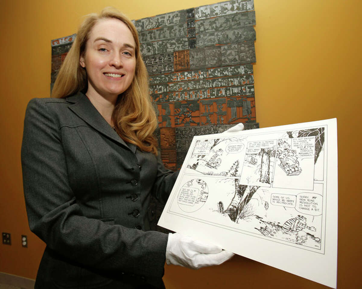"""In this Wednesday, Oct. 23, 2013 photo shows Juli Slemmons holding a """"Calvin and Hobbes"""" comic by cartoonist Bill Watterson at the Billy Ireland Cartoon Library & Museum in Columbus, Ohio. Today the museum collection includes more than 300,000 original strips from everybody who?'s anybody in the newspaper comics world, plus 45,000 books, 29,000 comic books and 2,400 boxes of manuscript material, correspondence and other personal papers from artists. (AP Photo/Tony Dejak)"""