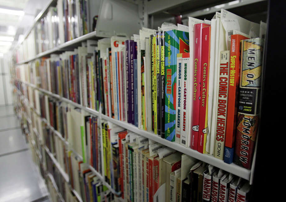 In this Wednesday, Oct. 23, 2013 photo shows rows of books on cartoons at the Billy Ireland Cartoon Library & Museum in Columbus, Ohio. Today the museum collection includes more than 300,000 original strips from everybody who's anybody in the newspaper comics world, plus 45,000 books, 29,000 comic books and 2,400 boxes of manuscript material, correspondence and other personal papers from artists. (AP Photo/Tony Dejak) / AP