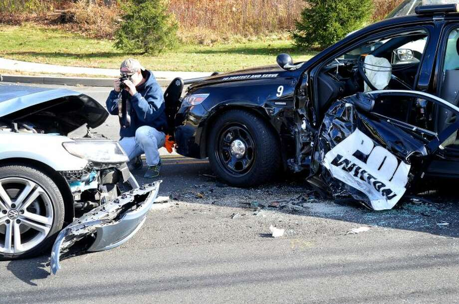 Hour Photo/Alex von Kleydorff. Wilton Police Detective Peter Trahan takes photos of the two vehicles involved in an accident on Danbury Rd, in Wilton Monday morning. A Wilton Police cruiser was involved with a Volkswagen sedan and both drivers had to be extrictaed from their vehicles.