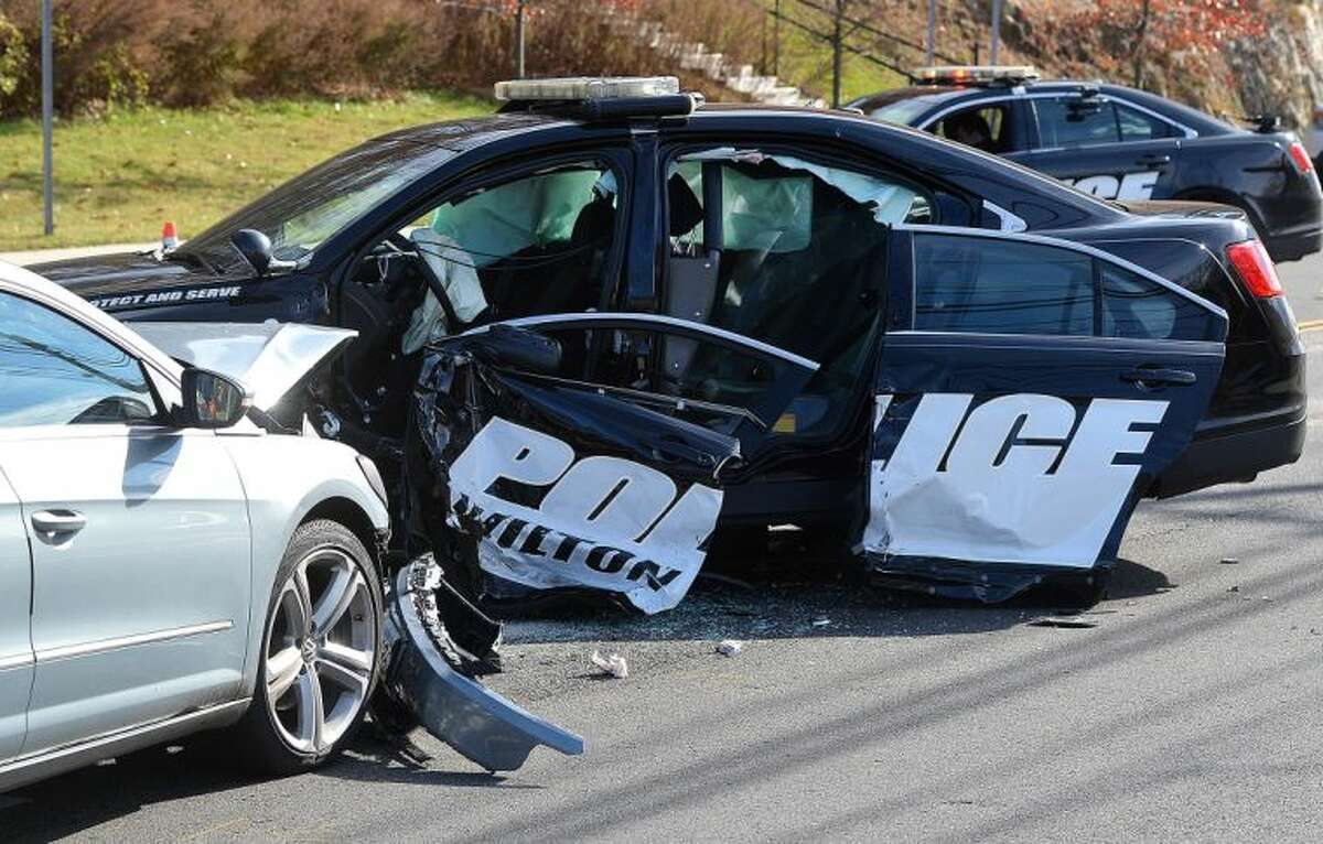 Hour Photo/Alex von Kleydorff. Wilton Police inestigate the two vehicles involved in an accident on Danbury Rd, in Wilton Monday morning. A Wilton Police cruiser was involved with a Volkswagen CC sedan and both drivers had to be extrictaed from their vehicles.