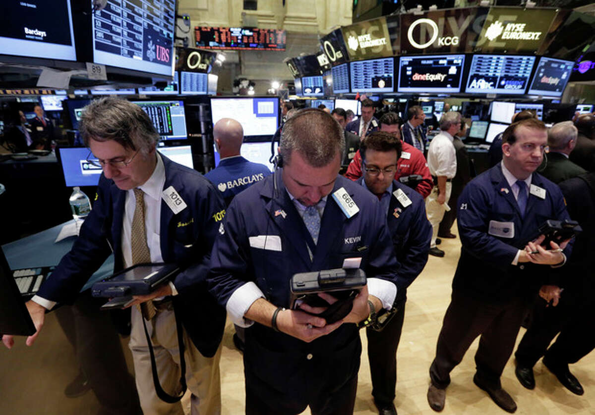 People on the floor of the New York Stock Exchange observe a moment of silence on Veteran's Day, Monday, Nov. 11, 2013. (AP Photo/Richard Drew)