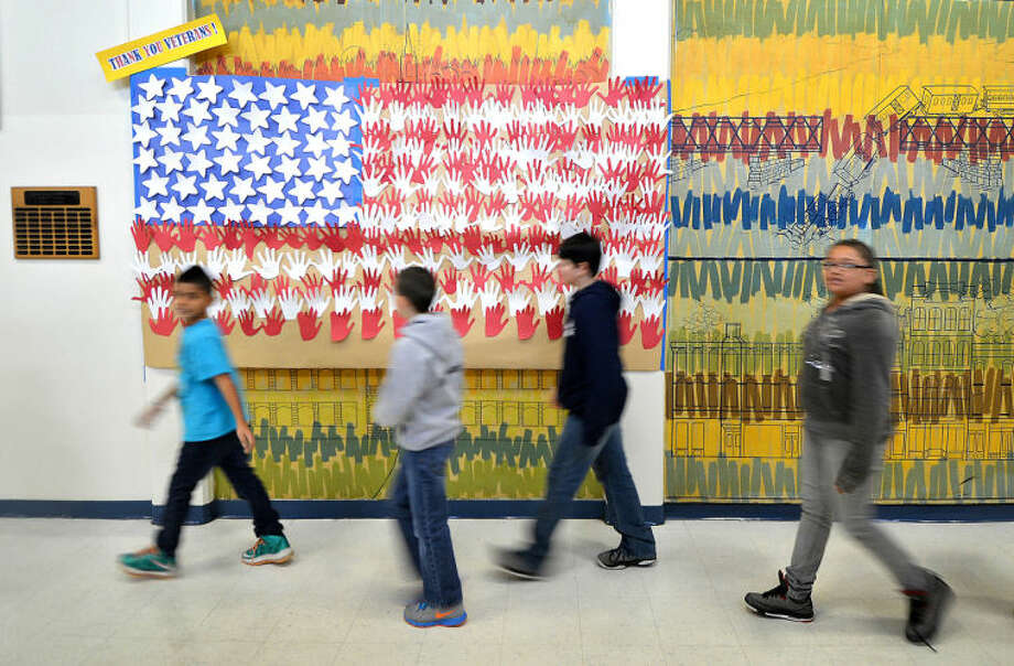 Hour Photo/Alex von Kleydorff. Over 200 hands signed by 6th graders make up a giant United States flag that hangs as a Thank you, in the hallway at Nathan Hale School for Veterans Day.