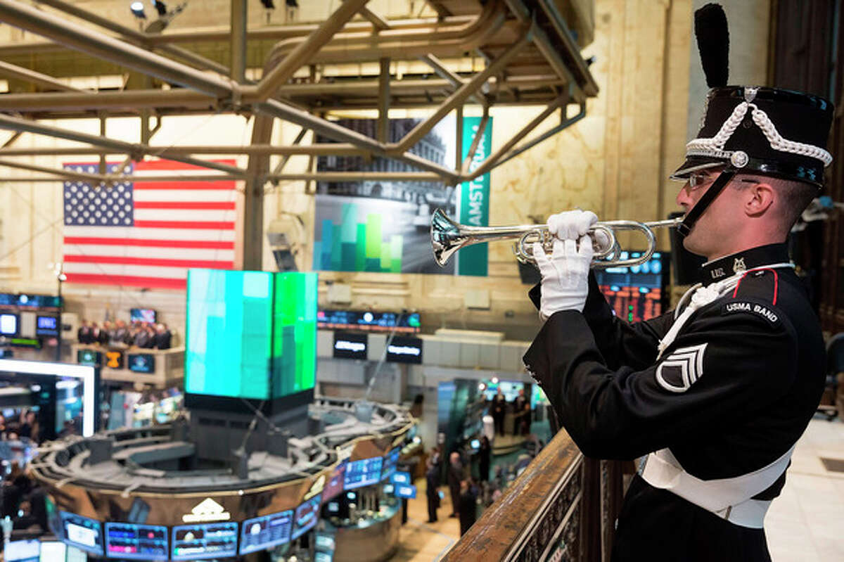 Staff Sgt. Bryan McKinney, of the U.S. Military Academy Band at West Point , plays Taps on a balcony of the New York Stock Exchange, in honor of Veteran's Day, Monday, Nov. 11, 2013. (AP Photo/Ben Hider, NYSE)