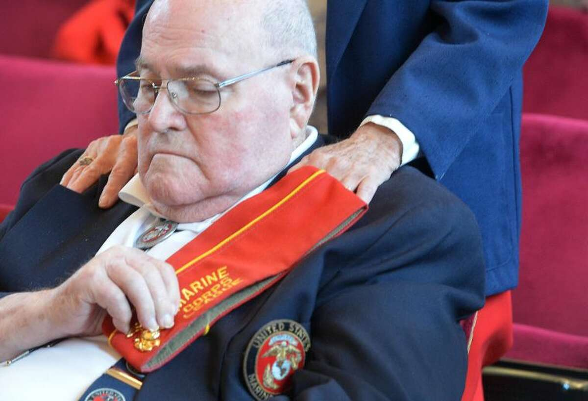 Hour Photo/Alex von Kleydorff. Theresa Kish puts her hands on the shoulders of U.S.M.C Veteran Earl Carpenter during a solemn moment at Norwalks Veeterans Day ceremony at City Hall