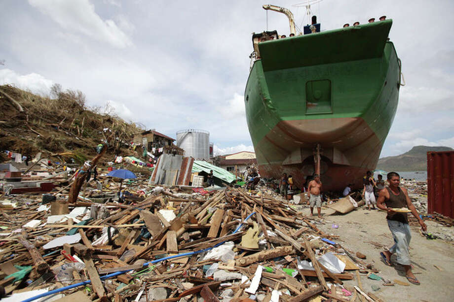 A survivor walks beside a ship that was washed ashore hitting makeshift houses near an oil depot in Tacloban city, Leyte province central Philippines on Monday, Nov. 11, 2013. Authorities said at least 2 million people in 41 provinces had been affected by Friday's typhoon Haiyan and at least 23,000 houses had been damaged or destroyed. (AP Photo/Aaron Favila) / AP