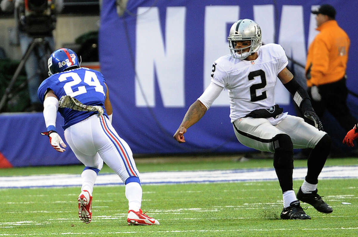 New York Giants cornerback Terrell Thomas (24) escapes Oakland Raiders quarterback Terrelle Pryor (2) after intercepting from Pryor during the second half of an NFL football game on Sunday, Nov. 10, 2013, in East Rutherford, N.J. (AP Photo/Bill Kostroun)