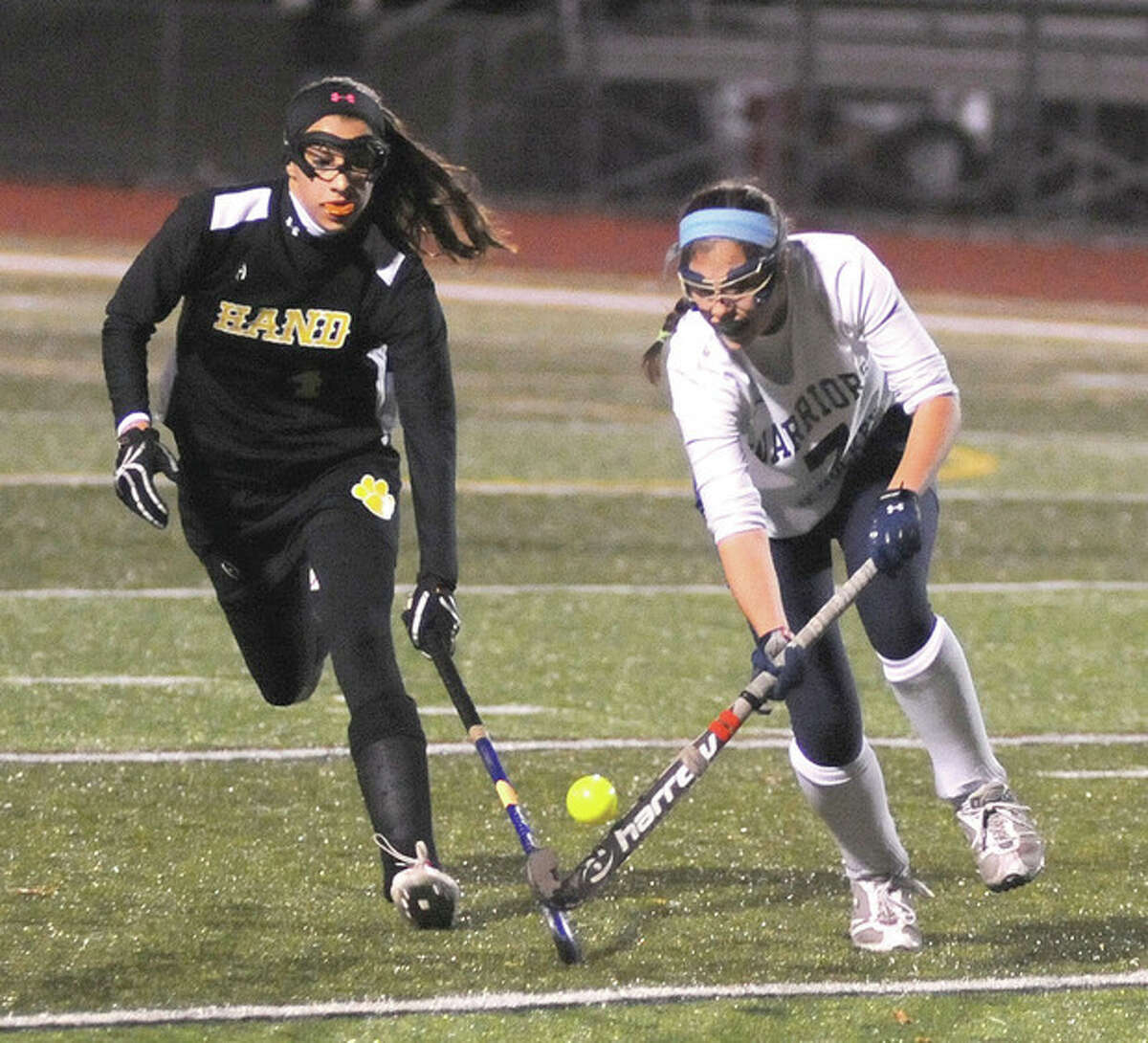 Hour photo/John Nash Annie Cornbooks of Wilton, right, gets to the ball ahead of a Daniel Hand player during Tuesday's Class M semifinal in Cheshire.