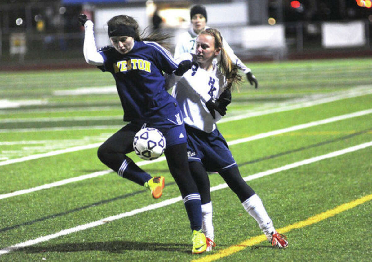 Hour photo/Matthew Vinci Weston's Shelby Merlberg, left, and Haddam-Killingworth's Molly Madore battle for the ball during Tuesday's Class M semifinal game.