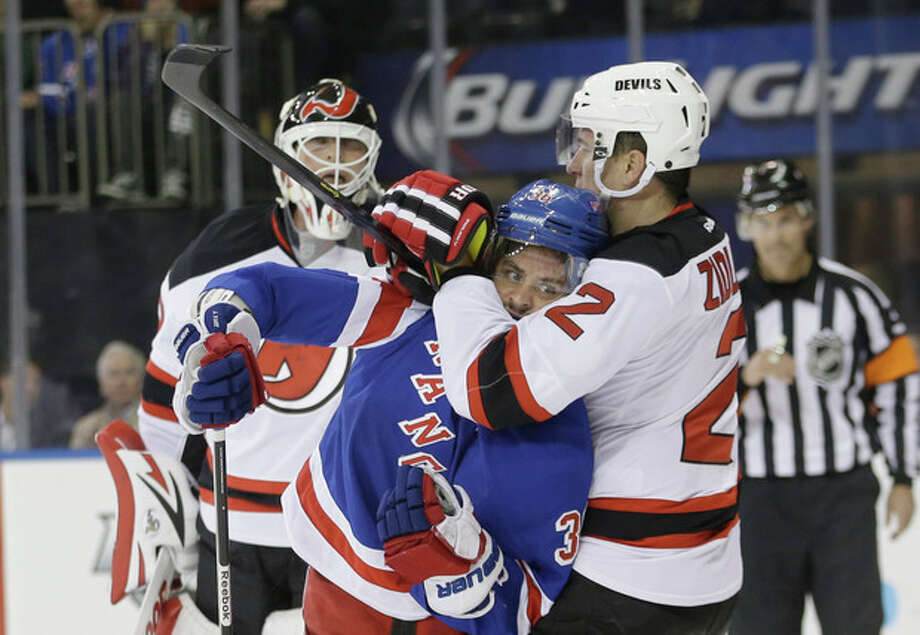 New Jersey Devils' Marek Zidlicky (2) grabs New York Rangers' Mats Zuccarello (36) as Devils goalie Martin Brodeur watches during the second period of an NHL hockey game Tuesday, Nov. 12, 2013, in New York. (AP Photo/Frank Franklin II) / AP