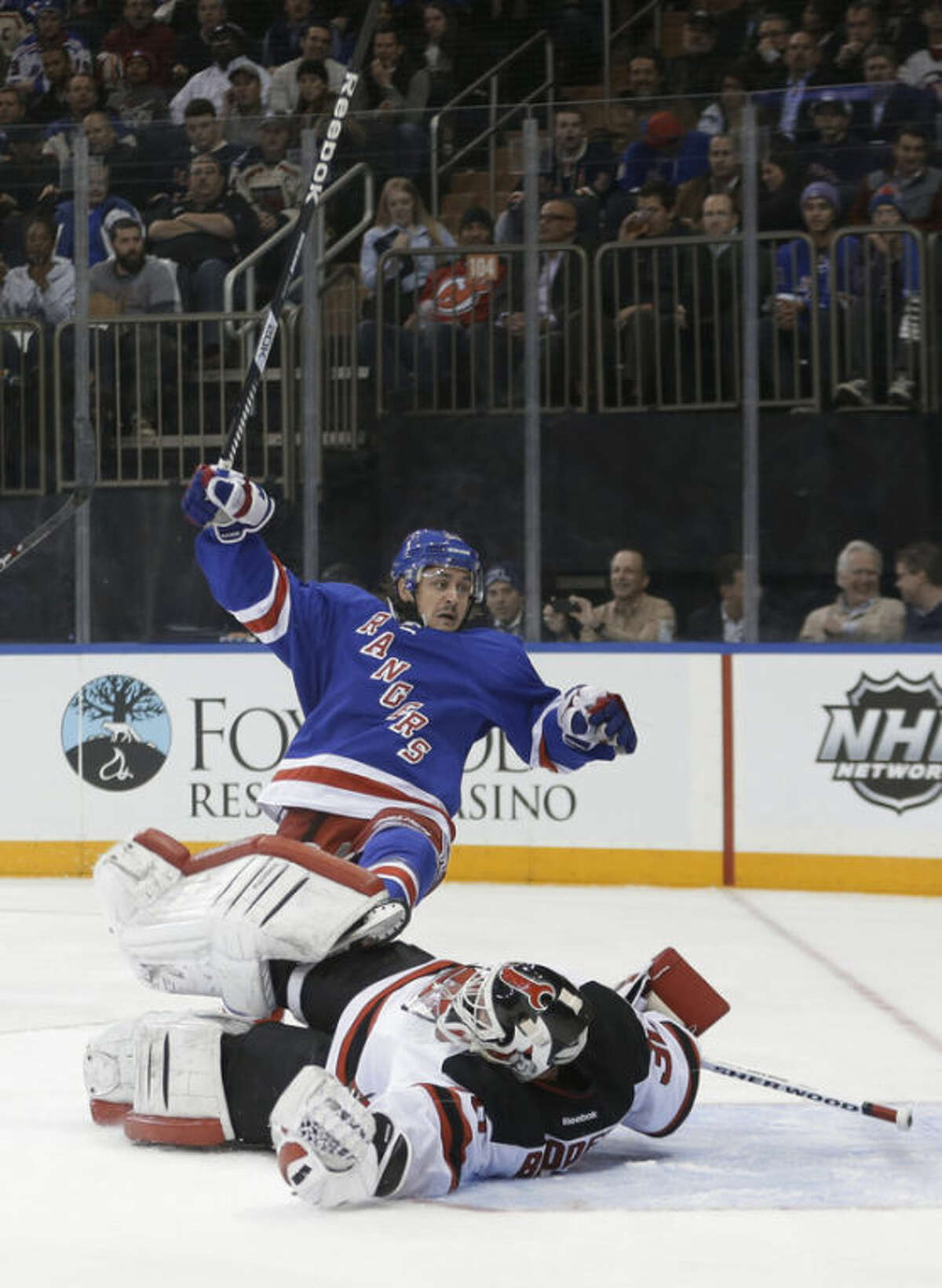 New Jersey Devils goalie Martin Brodeur (30) stops a shot as New York Rangers' Mats Zuccarello (36) looks for the puck during the second period of an NHL hockey game Tuesday, Nov. 12, 2013, in New York. (AP Photo/Frank Franklin II)