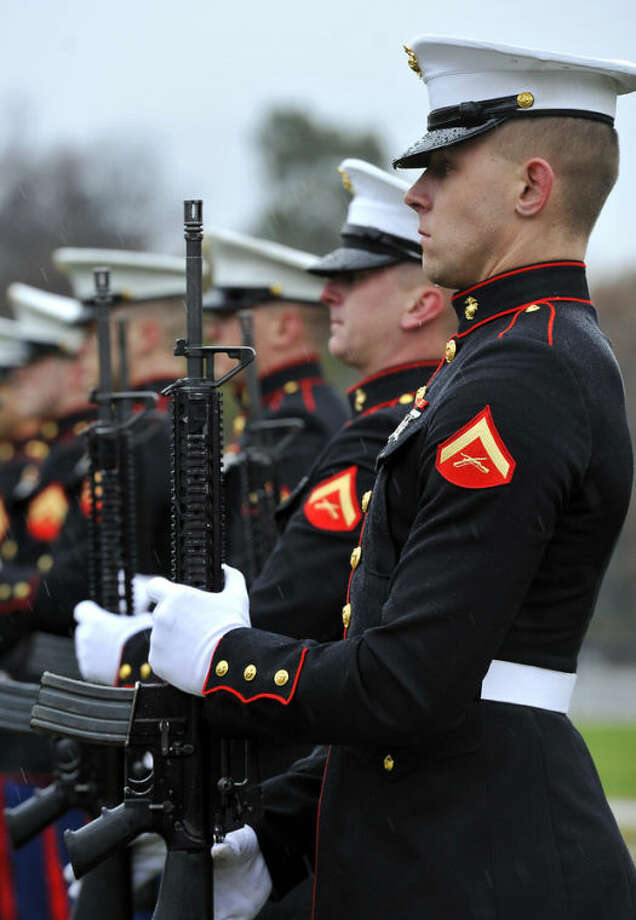 Marines stand in the cold rain after a 21-gun salute during the Medal of Honor Memorial Dedication ceremonies for U.S. Marine Corps Reserve 2nd Lt. Sherrod E. Skinner Jr. outside the Hannah Community Center in East Lansing Monday, Nov. 11, 2013. Skinner, who was from East Lansing, is a postumous recipient of the Medal of Honor for bravery in the Korean War. (AP Photo/The State Journal, Rod Sanford) NO SALES