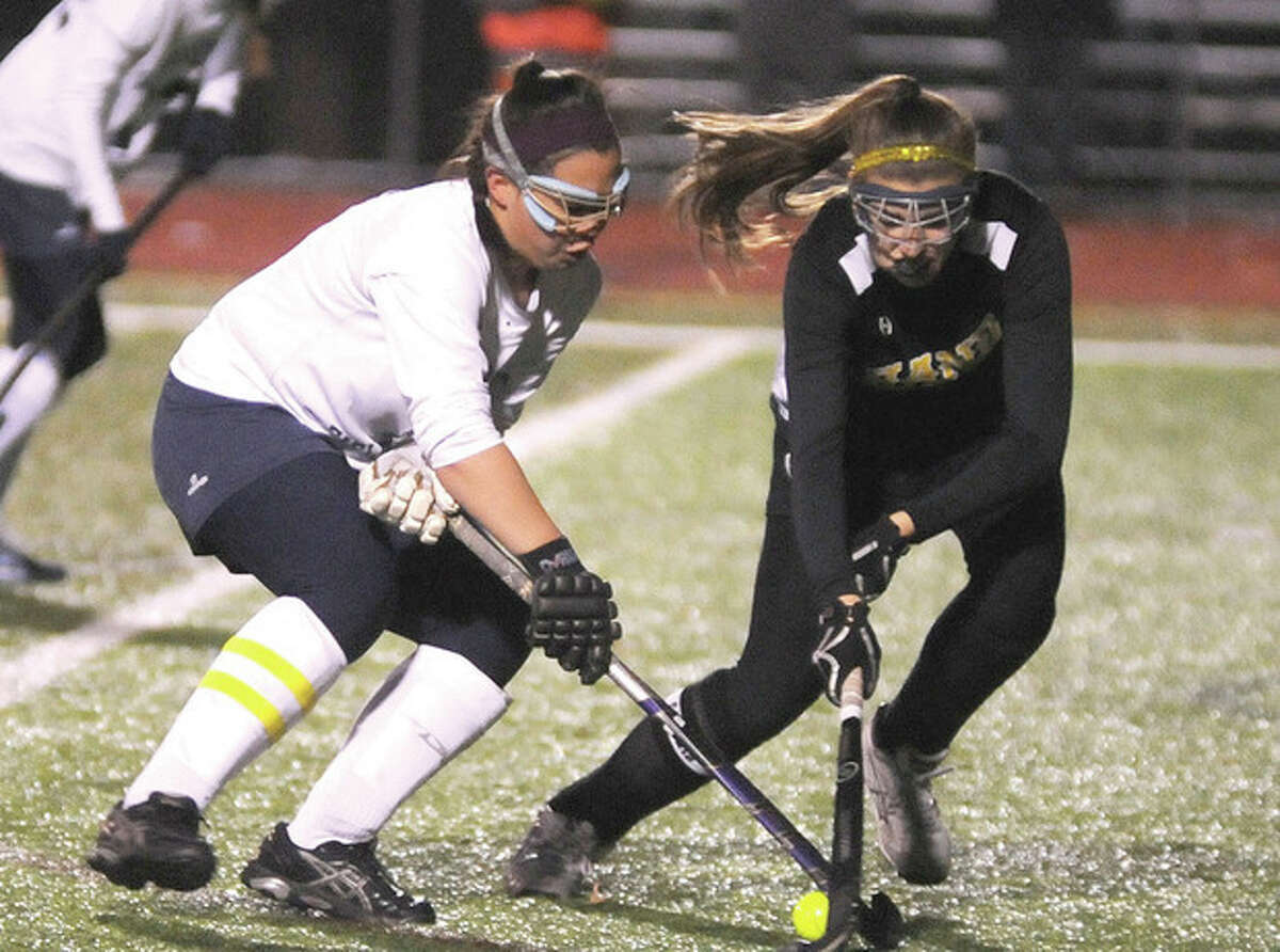 Hour photo/John Nash Jill Detrick-Yee of Wilton, left, battles with a Daniel Hand defender for control of the ball during Tuesday night's Class M semifinal in Cheshire. The Warriors won, 2-1, to advance to the class final.