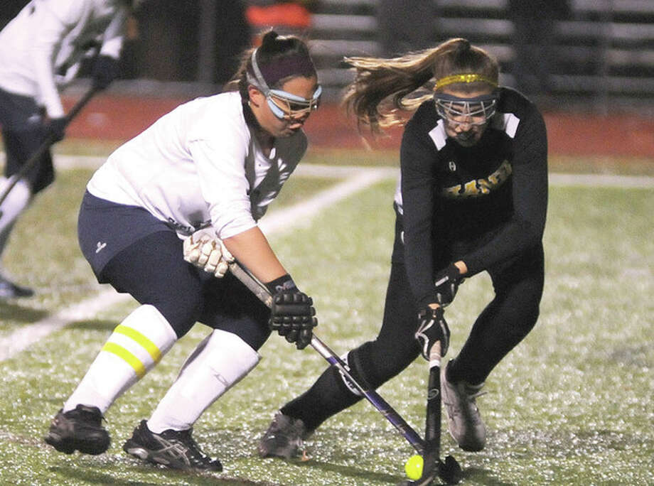 Hour photo/John NashJill Detrick-Yee of Wilton, left, battles with a Daniel Hand defender for control of the ball during Tuesday night's Class M semifinal in Cheshire. The Warriors won, 2-1, to advance to the class final.