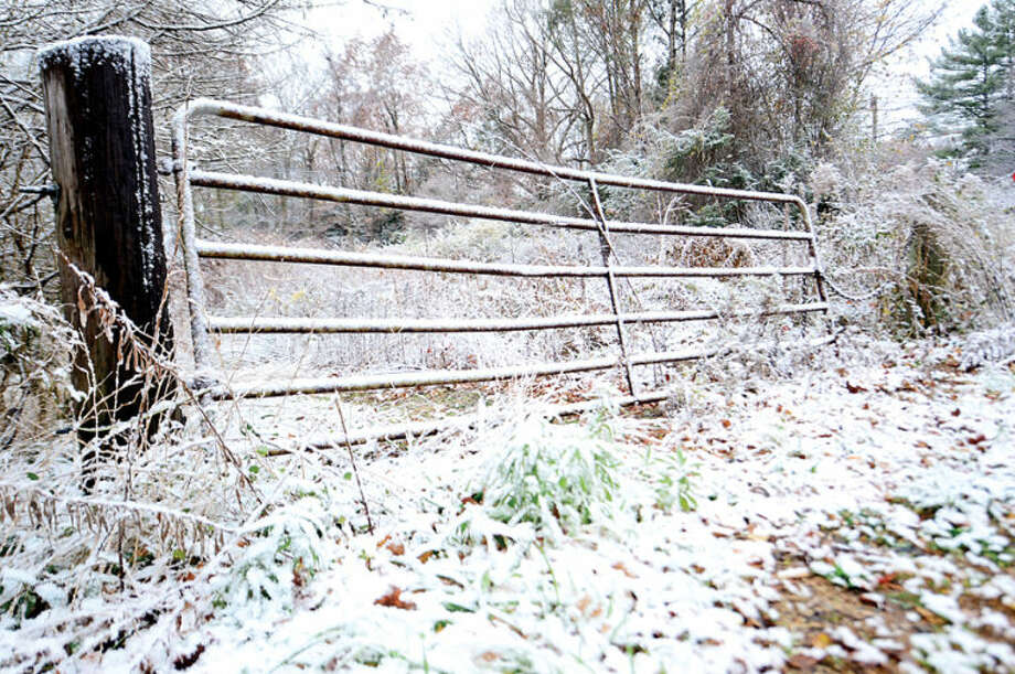 Hour photo / Erik Trautmann A light coating of snow covers a gate off Scribner Avenue Tuesday morning .
