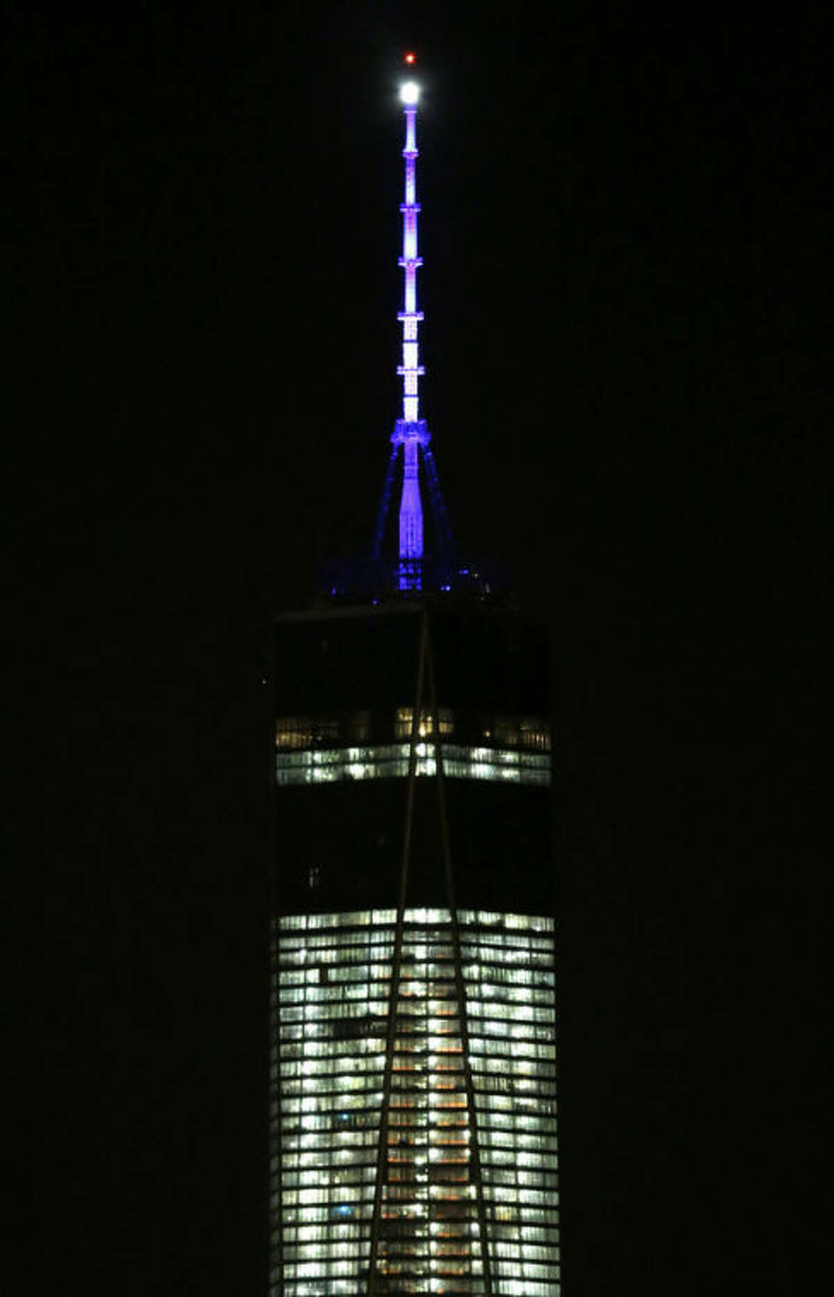 FILE - In this Nov. 8, 2013 file photo, the beacon and spire of 1 World Trade Center are lit up, as seen from The Heights neighborhood of Jersey City, N.J. The new World Trade Center tower in New York knocked Chicago's Willis Tower off its pedestal as the nation's tallest building when an international panel of architects announced Tuesday, Nov. 12, 2013 that the needle atop the skyscraper can be counted when measuring the structure's height. (AP Photo/Julio Cortez, File)