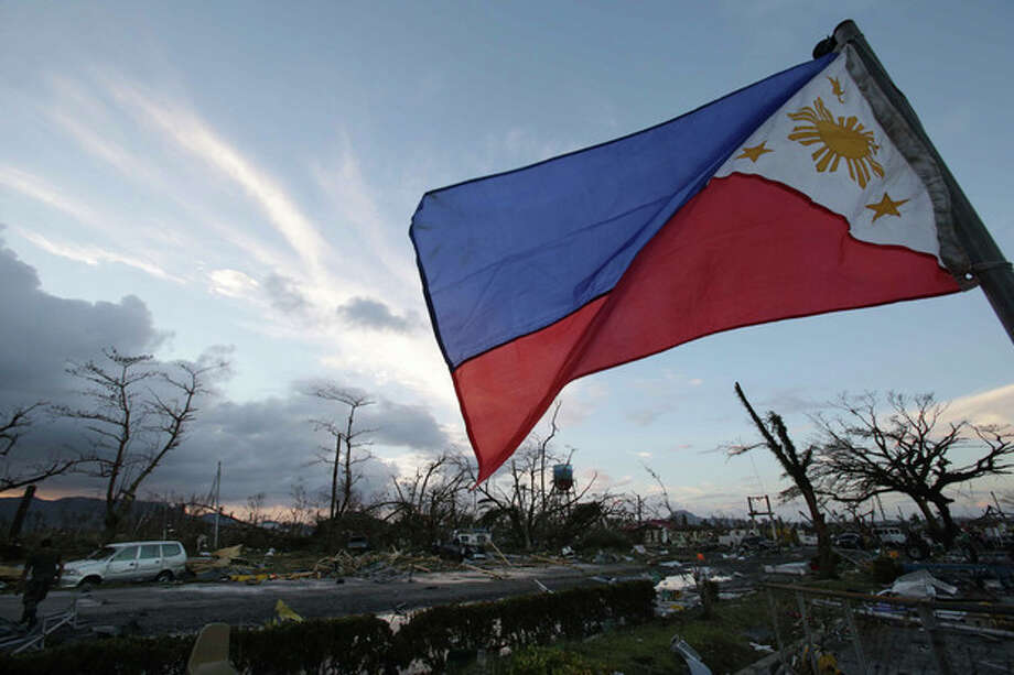 FILE - In this Saturday, Nov. 9, 2013 file photo, a Philippine flag stands amongst the damage caused after powerful Typhoon Haiyan slammed into Tacloban city, Leyte province, central Philippines. Haiyan slammed the island nation with a storm surge two stories high and some of the highest winds ever measured in a tropical cyclone. An untold number of homes were blown away, and thousands of people are feared dead. (AP Photo/Aaron Favila, File) / AP