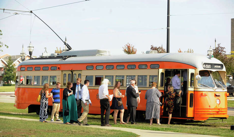 In this Sept. 28, 2013 photo, passengers board the Johnstown (Kenosha) streetcar during Kenosha Streetcar Day in Kenosha, Wis. Long after the streetcar was driven to the edge of extinction in America by the automobile _ hanging on only in a few places like New Orleans and Philadelphia _ cities are spending millions putting them back in, often along the same stretches of pavement where rail was wrenched out decades ago. The idea is that streetcars can form the heart of communities built around them, igniting economic development in urban centers that badly need it and offering a whiff of excitement to boot. (AP Photo/Michael Schmidt) / FR171004 AP