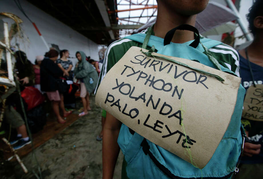 Typhoon survivors hang signs from their necks as they queue up in the hopes of boarding a C-130 military transport plane Tuesday, Nov. 12, 2013, in Tacloban, central Philippines. Thousands of typhoon survivors swarmed the airport on Tuesday seeking a flight out, but only a few hundred made it, leaving behind a shattered, rain-lashed city short of food and water and littered with countless bodies. The typhoon, known as Haiyan elsewhere in Asia but called Yolanda in the Philippines, was likely the deadliest natural disaster to beset this poor Southeast Asian nation. (AP Photo/Bullit Marquez) / AP