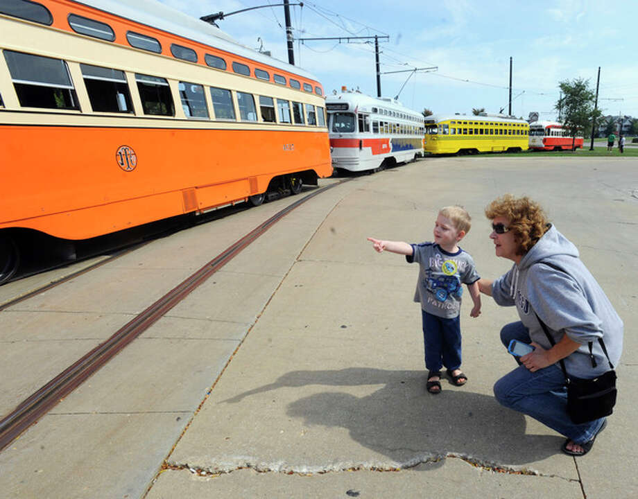 In this Sept. 28, 2013 photo, Johnathan Sainski, 2, of Wheatland, Wis., points out his favorite streetcar to his grandmother Anna Sainski, of Bristol, Wis., during Kenosha Streetcar Day outside the Joseph McCarthy Transit Center in Kenosha, Wis. From left are the Johnstown (Kenosha), Southeastern Pennsylvania, Cincinnati and the Pittsburgh streetcars. When the city of Kenosha lost the auto plant that employed thousands, the a bruised community in southern Wisconsin plucked something unexpected from its pre-automobile past to help reinvent the city and fill its depressed downtown with life. They brought back their street cars, sending brightly colored antique trolleys creeping along a two-mile loop around the city and along the lake Michigan shore. (AP Photo/Michael Schmidt) / FR171004 AP