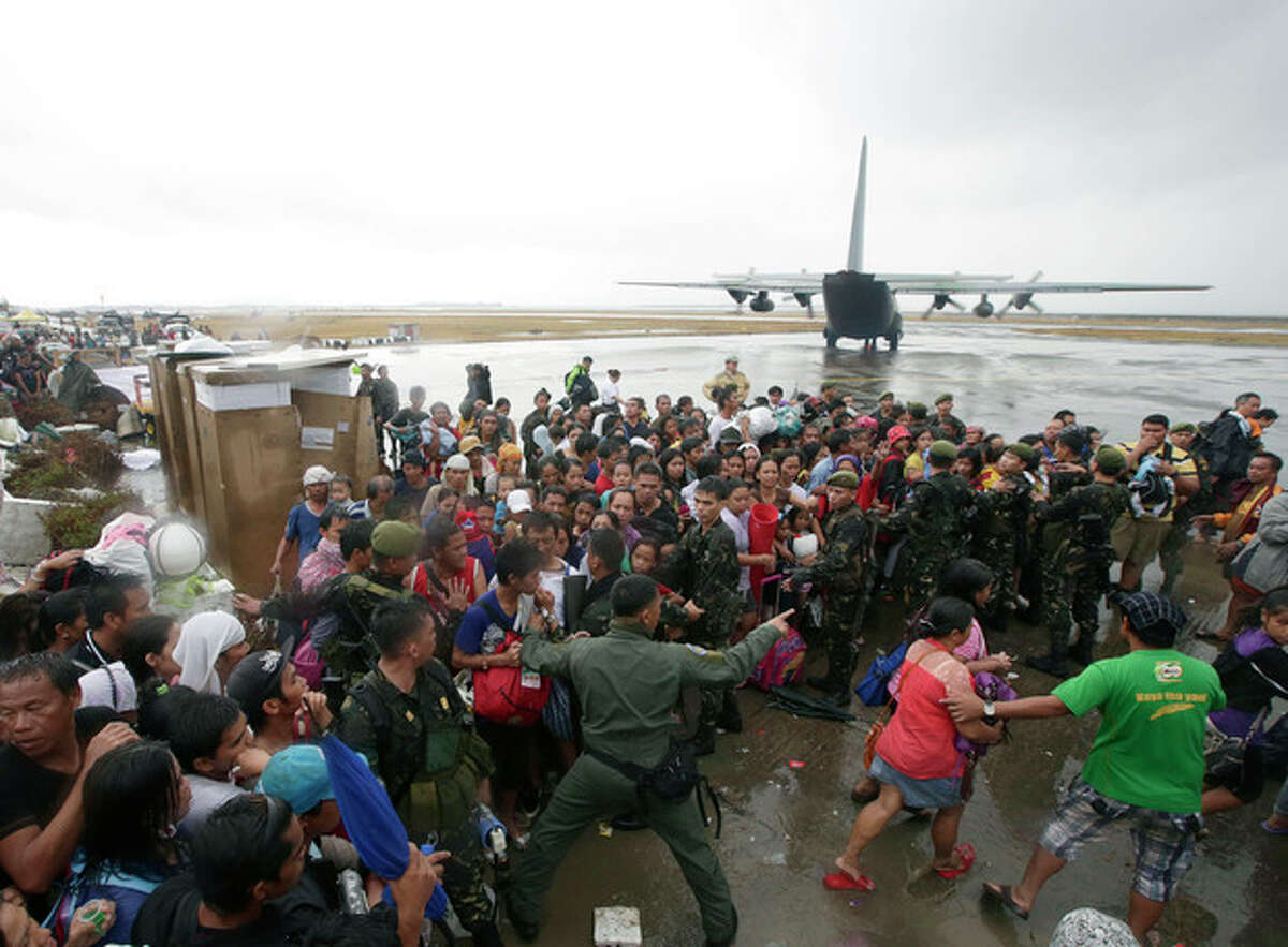 Typhoon survivors rush to get a chance to board a C-130 military transport plane in Tacloban city, Leyte province, central Philippines, Tuesday, Nov. 12, 2013. Thousands of typhoon survivors swarmed the airport in the city of Tacloban in the central Philippines seeking a flight out, but only a few hundred made it, leaving behind a shattered, rain-lashed city short of food and water and littered with countless bodies. (AP Photo/Bullit Marquez)