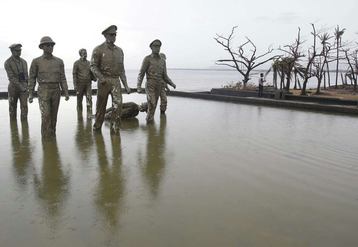 One of seven statues of the team of U.S. General Douglas MacArthur reeanacting his historic landing is toppled as it was hit by strong winds during Typhoon Haiyan in Tacloban city, Leyte province, central Philippines on Tuesday, Nov. 12, 2013. Four days after Typhoon Haiyan struck the eastern Philippines, assistance is only just beginning to arrive. Authorities estimated the storm killed 10,000 or more across a vast swath of the country. (AP Photo/Aaron Favila)
