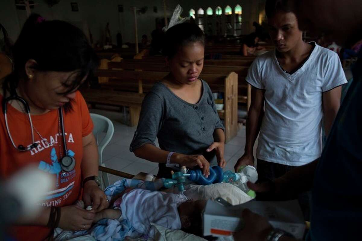 Genia Mae Mustacisa, center, pumps oxygen into the lungs of her three-day-old infant in front of the altar of a Catholic chapel inside the Eastern Visayas Regional Medical Center in Tacloban on Saturday Nov. 16, 2013. On the right is her husband Emmanuel Barrico. The chapel is now being used to care for infants after Typhoon Haiyan destroyed the original facility of the hospital. (AP Photo/David Guttenfelder)