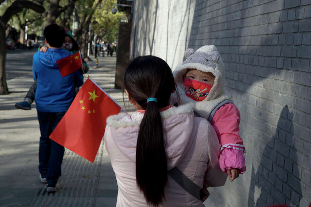 Visitors to the forbidden city carry children holding the Chinese national flags in Beijing, China, Saturday, Nov. 16, 2013. Some 15 million to 20 million Chinese parents will be allowed to have a second baby after the Chinese government announced Friday, Nov. 15, 2013 that couples where one partner has no siblings can have two children, in the first significant easing of the country?'s strict one-child policy in nearly three decades.(AP Photo/Ng Han Guan)