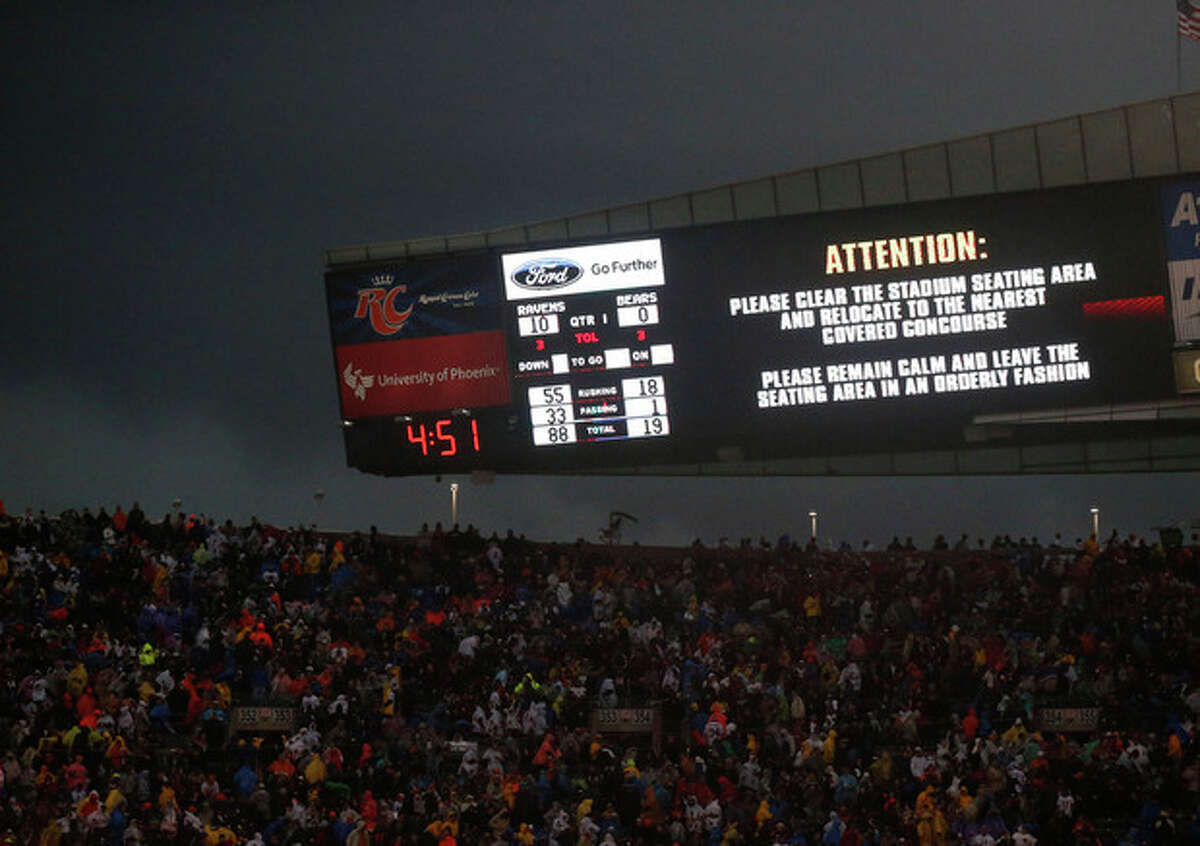 Fans are warned to take cover as a severe storm moves through Soldier Field during the first half of an NFL football game between the Chicago Bears and Baltimore Ravens, Sunday, Nov. 17, 2013, in Chicago. (AP Photo/Charles Rex Arbogast)